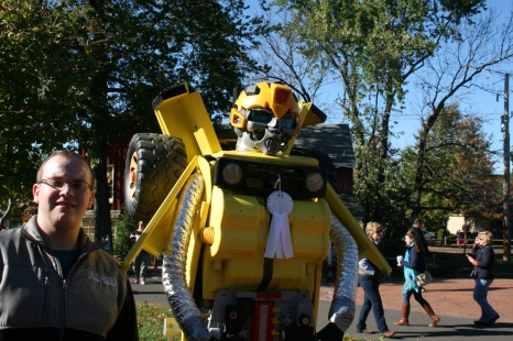 Sean posing with a scarecrow based on a Transformer character!